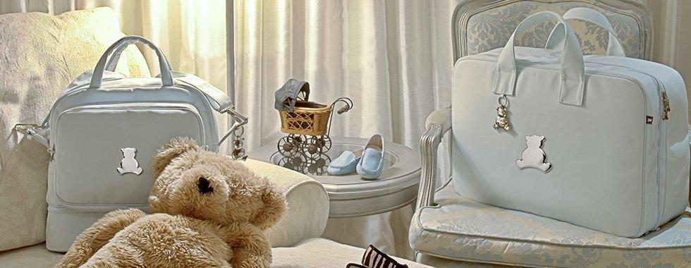 Foto dos primórdios da marca de bolsa maternidade com um urso de pelúcia e duas bolsas azuis